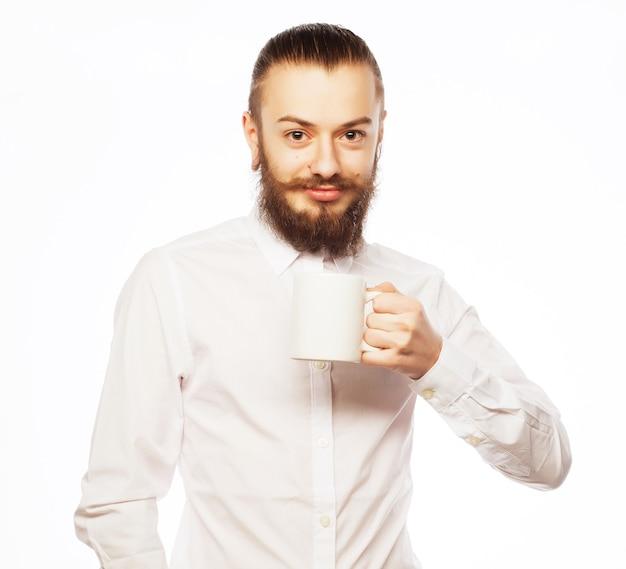 Молодой человек пьет чашку кофе или чая на белом фоне