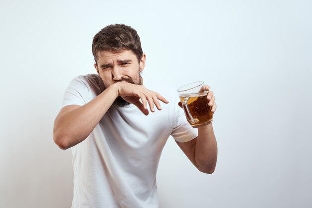 Молодой человек пьет стакан пива изолированные