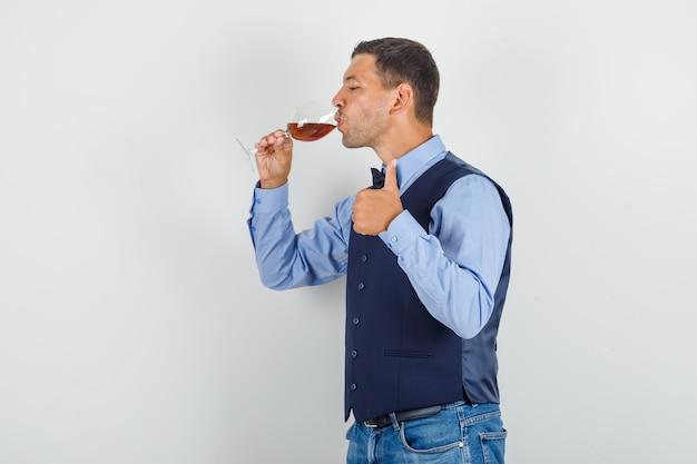 Молодой человек пьет алкоголь и показывает палец вверх в костюме, джинсах и выглядит довольным. .