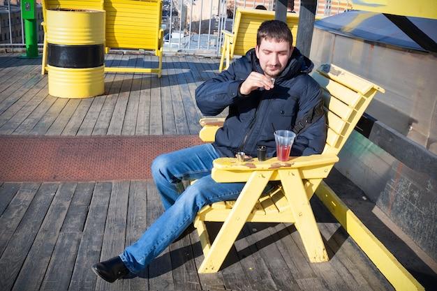 ブルージーンズと暖かいジャケットで日当たりの良いテラスの木製の黄色い椅子に座って、小さなガラスからアルコールを飲む若い男。