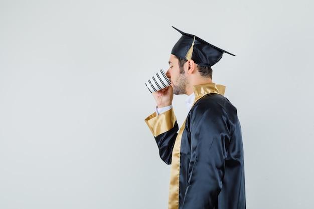 Giovane uomo che beve caffè aromatico in uniforme laureato.