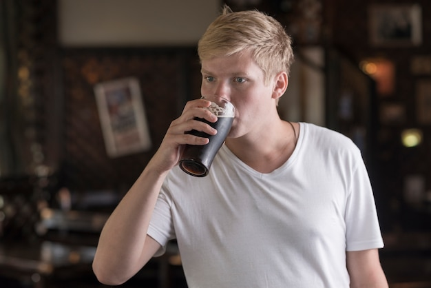Young man drinking beer in pub