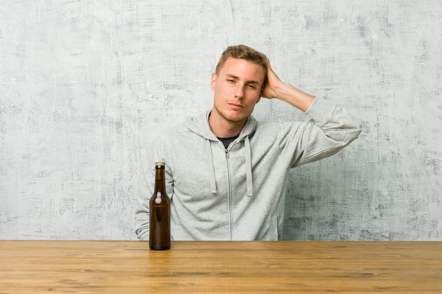 Young man drinking a beer on a table being shocked, she has remembered important meeting.