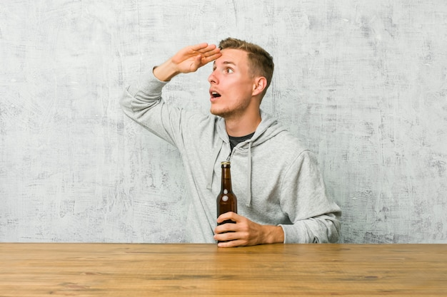 Young man drinking a beer on a table looking far away keeping hand on forehead.