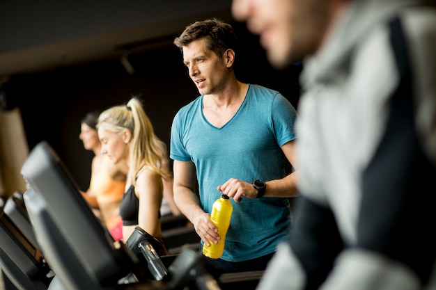 Young man drinking bottle of water on threadmill in gym