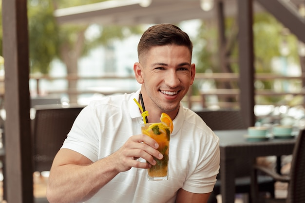 Young man drinking cocktail in beach cafe