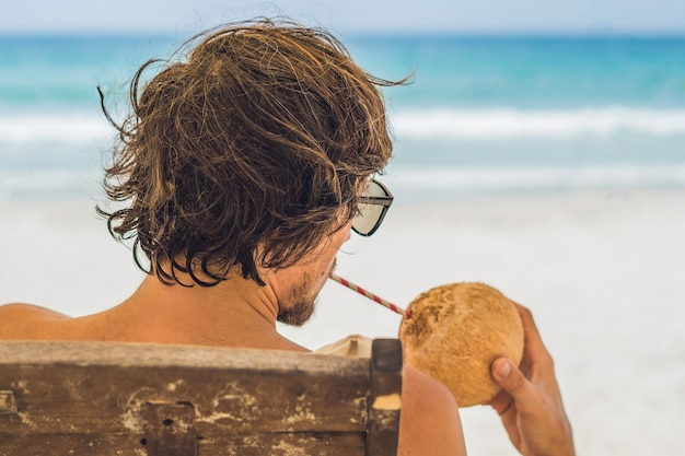 Young man drinking coconut milk on chaise-longue on beach