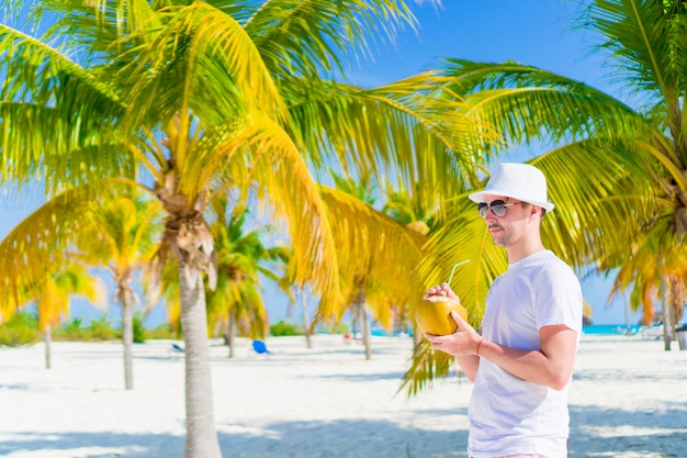 Young man drinking coconut milk on hot day on the beach in palm grove
