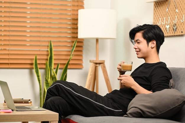 Молодой человек пьет кофе и имеет видеозвонок на портативном компьютере.