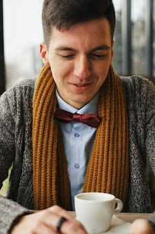 Young man drinking coffee in cafe and using a mobile phone