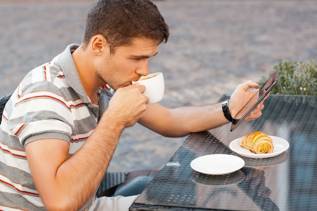 タブレットを持ってコーヒーを飲む若い男