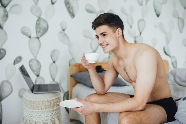 Молодой человек пьет кофе в постели