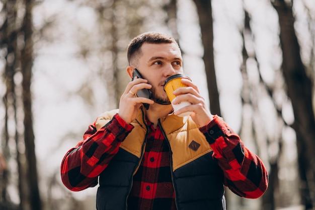 Молодой человек пьет кофе в парке и с помощью телефона