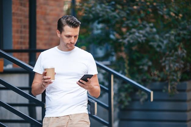 Молодой человек пьет кофе в городе на открытом воздухе