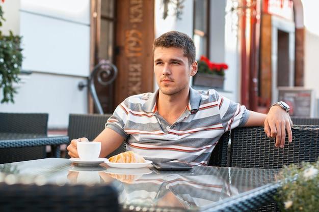 テーブルで外でコーヒーを飲む若い男