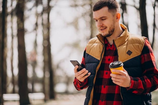 Caffè bevente del giovane in parco e nel telefono usando