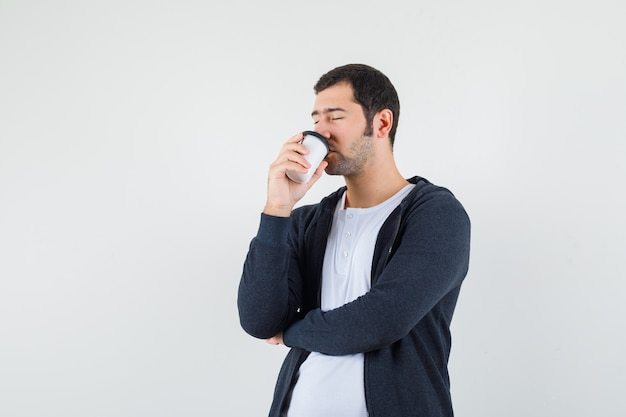 Young man drinking coffee in white t-shirt and zip-front black hoodie and looking calm , front view.