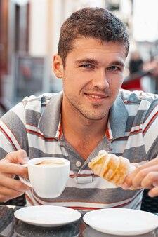 クロワッサンとコーヒーを飲む若い男