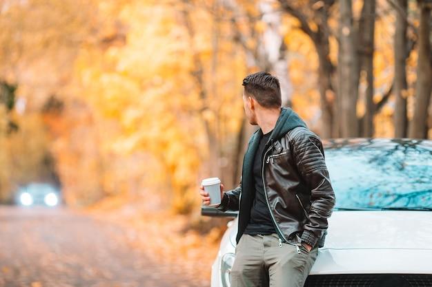 秋の公園屋外で電話でコーヒーを飲む若い男