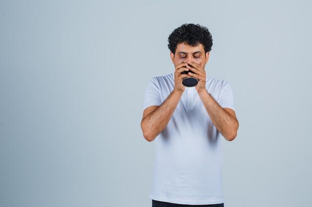 白いtシャツとジーンズでお茶を飲み、喉が渇いた、正面図を探している若い男。