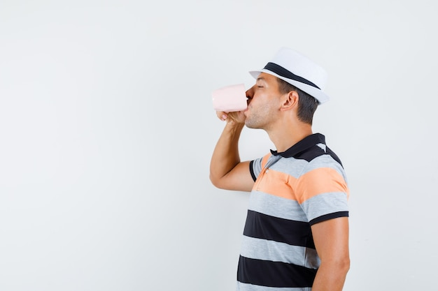 Young man drinking cup of tea in t-shirt and hat and looking delighted