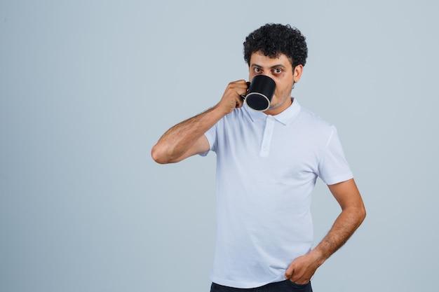 Giovane uomo che beve una tazza di tè mentre tiene la mano sulla vita in maglietta bianca e jeans e sembra serio. vista frontale.