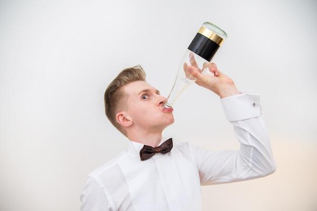 흰색 배경에 대해 유리 병에서 마시는 젊은 남자. 명랑 한 얼굴입니다.