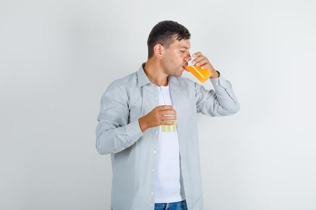 シャツにジュースのガラスを飲む若い男