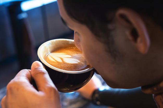 若い男がカフェでホットコーヒーを飲む
