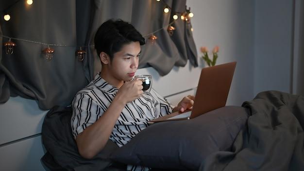 Молодой человек, пить горячий чай и портативный компьютер на кровати ночью.