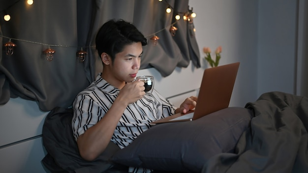 Young man drinking hot tea and laptop computer on bed at night.