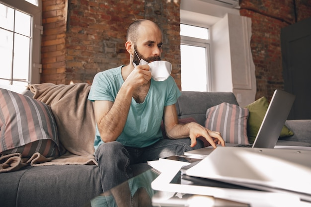 Young man drinking tea at home while working