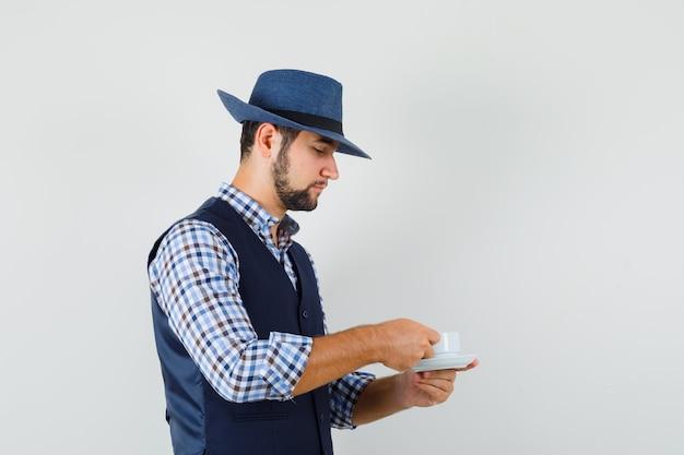 Giovane che beve il tè in camicia, gilet, cappello e guardando attento. .