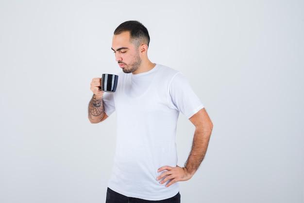 白いtシャツと黒いズボンで腰に手を握り、真剣に見ながらお茶を飲む若い男