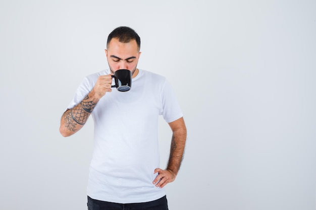 Young man drinking tea while holding hand on waist in white t-shirt and black pants and looking serious