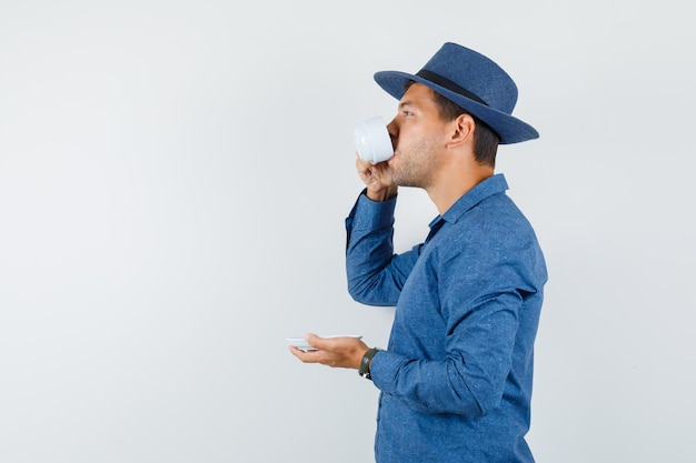 Young man drinking turkish coffee in blue shirt, hat .