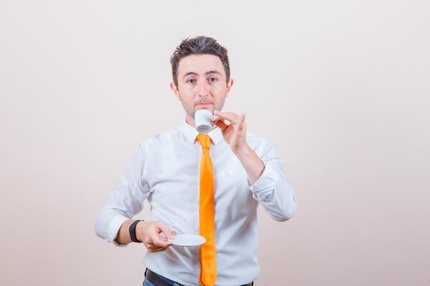 白いシャツ、ネクタイ、礼儀正しく見えるトルココーヒーを飲む若い男