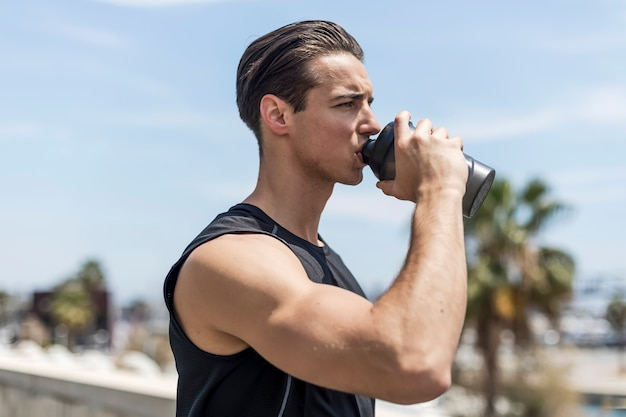 Young man drinking water after running portrait