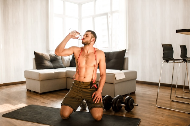 Young man drinking water after working out