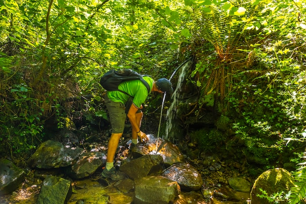 A young man drinking water from a natural source in monte igueldo, guipuzcoa,