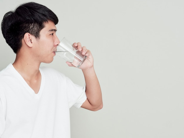 Young man drinking water of glass.