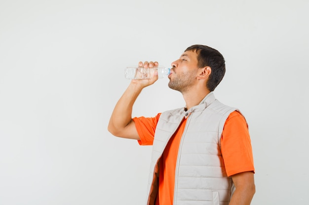 Young man drinking water in t-shirt, jacket and looking thirsty , front view.