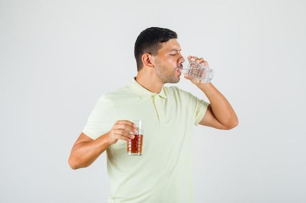 若い男がtシャツにコーラのガラスを押しながら水を飲む