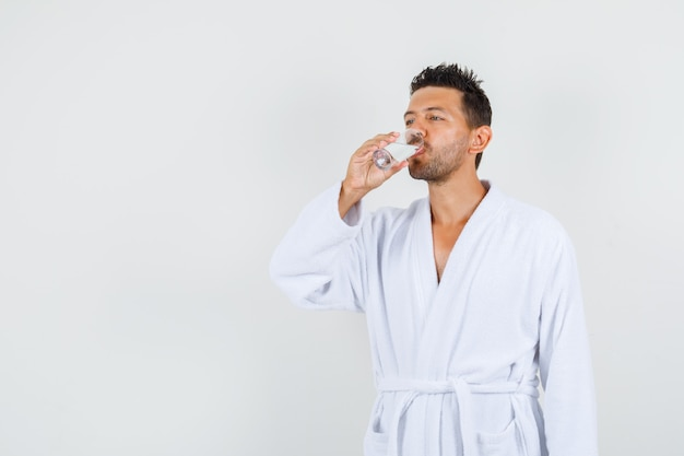 Young man drinking water in white bathrobe , front view.