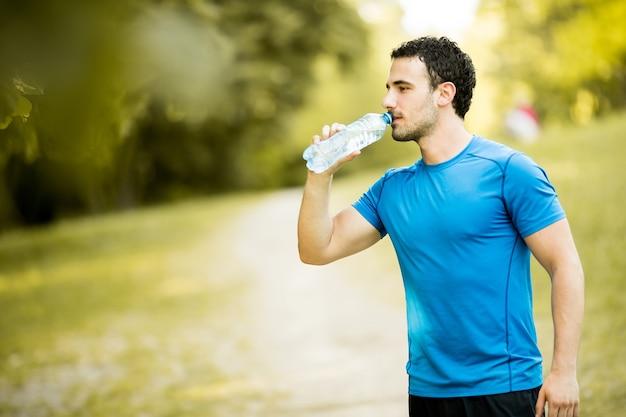 Молодой человек пьет воду