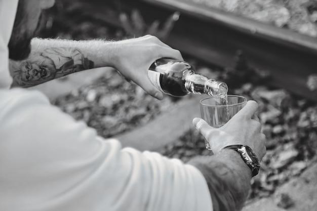 젊은 남자는 해질녘 시골의 버려진 철도에서 술을 마신다. 슬픔, 무관심, 우울증 또는 잘못된 생활 방식의 개념. 복사 공간