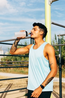 Young man drinks water after exercising in horizontal bar outdoors