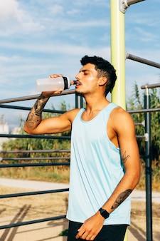 若い男が屋外の横棒で運動した後水を飲む
