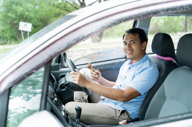 Young man driver relaxes inside a car using smartphone
