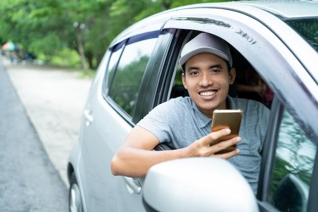 Young man driver use smartphone look at camera